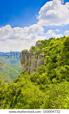 Rocks and Cross of San Miguel on top of cliff near the Montserrat Monastery, Catalonia, Spain  - stock photo