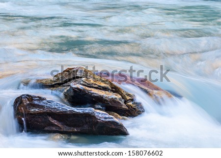Rocks in a rapid river - stock photo