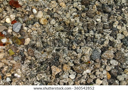 Rocks in bright clear water in sunshine texture - stock photo