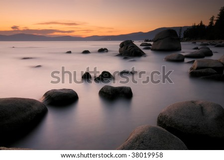 Rocks in the shallow waters of Lake Tahoe's Eastern Shore at sunset - stock photo