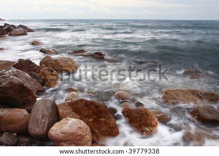 rocks in the water covered of foam and fog - stock photo