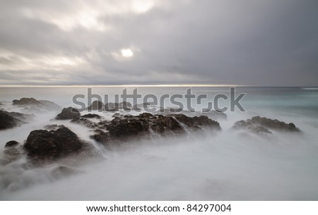 Rocks in the water with overcast sky near Big Sur, California - stock photo