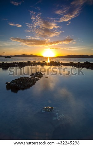 rocks in water and reflection of beautiful sunrise in water - stock photo