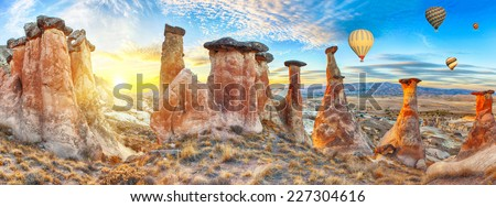 Rocks looking like mushrooms dramatically lit by a sunset in Cappadocia, Turkey. With balloons