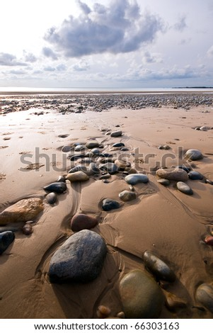 Rocks on Newborough beach - stock photo