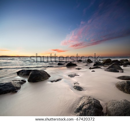 rocks on the beach with red clouds on square format - stock photo