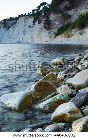rocks on the coast washed by the coastal waves. The sea is calm and the shore of the bay can be seen in the distance. On the hillside is a rare growth. - stock photo