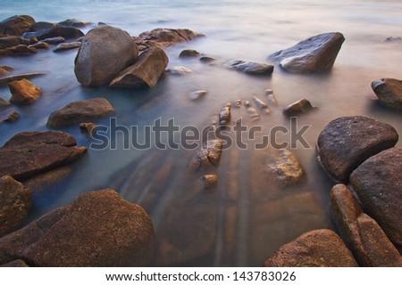 Rocks, sea, sunset on the  Tropical sea beach - stock photo