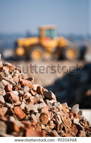 Rocks with excavator in background - stock photo