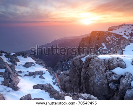 Rocks with snow during bright sundown. Natural composition - stock photo