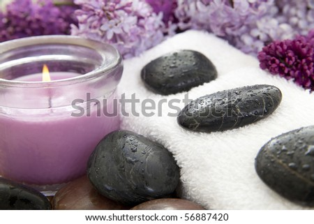 Rocks with water droplets on a white towel with a purple candle and lilac flowers. - stock photo