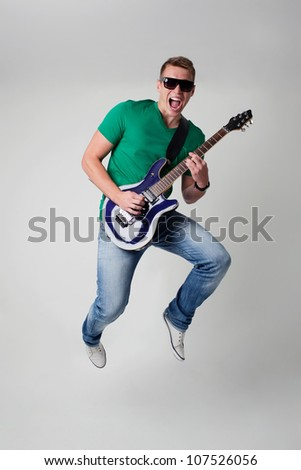 Rockstar leaping with guitar - stock photo