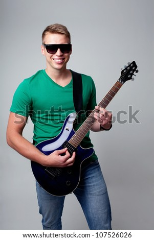 Rockstar  man playing on electric guitar - stock photo