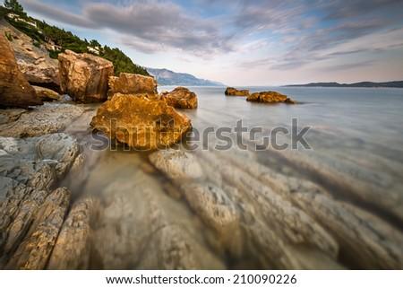 Rocky Beach and Transparent Adriatic Sea near Omis in the Evening, Dalmatia, Croatia - stock photo