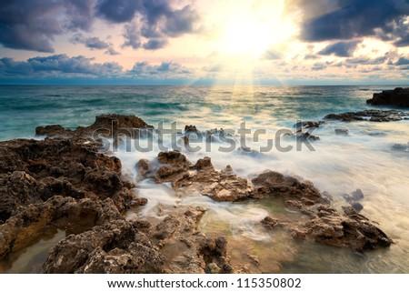 Rocky beach at sunset - stock photo
