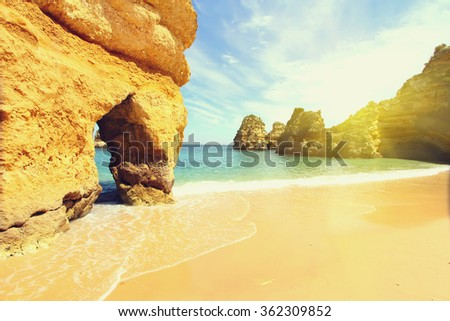 Rocky beach at sunset, Lagos, Portugal. Counter light. Vintage style. Travel and business background - stock photo