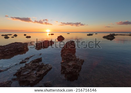 Rocky beach at sunset with vibrant colors - stock photo
