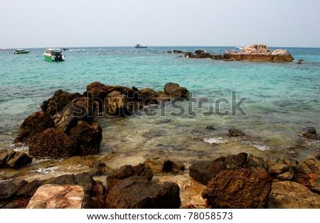 Rocky beach boat park Koh Larn Thailand - stock photo