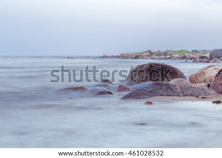 Rocky beach in summer early morning. Stones decorate the shoreline. The environment is calm and gentle, The sky merges with the horizon.