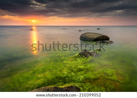 Rocky beach seascape at sunrise with small crabs on the rocks - stock photo