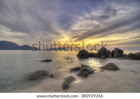 Rocky beach shot during sunset with dramatic sky and rock formation in the foreground - stock photo