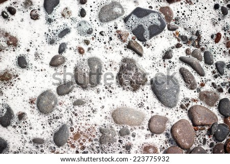Rocky beach with waves splashing on stones. - stock photo