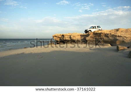 Rocky beach with 4x4 vehicle - stock photo
