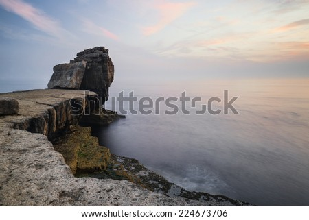 Rocky cliff landscape with sunset over ocean