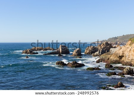 Rocky cliff on pacific ocean ocean shore in northern California with waves and rocks - stock photo