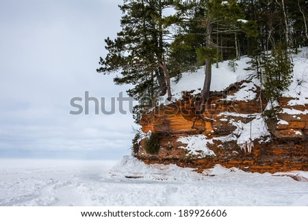 Rocky cliff / shoreline on frozen Lake Superior.  Highly textured rock.  Copy space to the left.  Apostle Island National Lakeshore on Lake Superior in Wisconsin, a popular winter travel destination. - stock photo