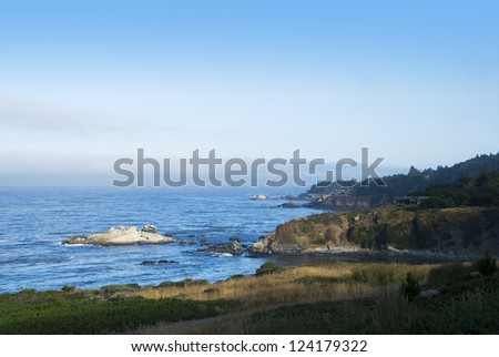 Rocky cliffs along the Pacific Ocean in Northern California.  There are distant homes seen on some of the promontories - stock photo