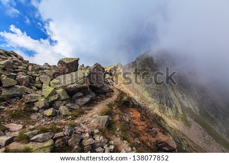 Rocky cliffs and storm clouds over French Alps, in summer - stock photo