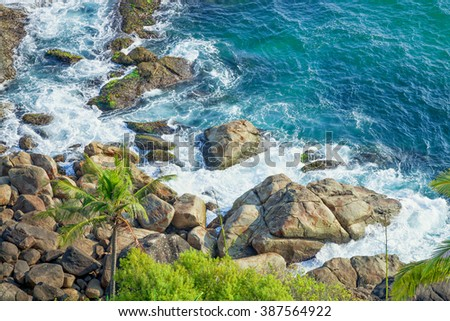 Rocky coast and clear turquoise sea. Thiruvananthapuram, India