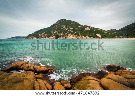 Rocky coast and view of  D'Aguilar Peak, at Shek O Beach, on Hong Kong Island, Hong Kong.