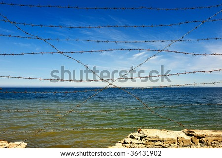 rocky coast with a wire entanglement barbed - stock photo