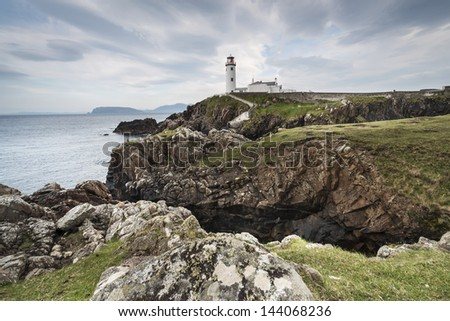 Rocky coastline and lighthouse, Fanad Head, County Donegal, Ireland - stock photo