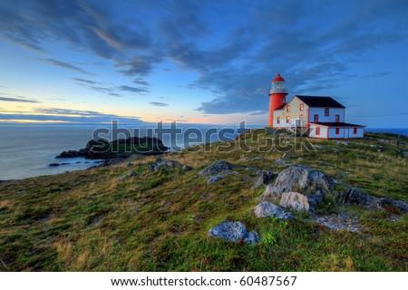 Rocky coastline with lighthouse. - stock photo