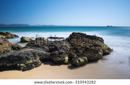 Rocky Coastline With Sand And Misty Ocean Below The Cape Byron Lighthouse And Overlooking the Julian Rocks Island with a Beautiful Clear Blue Sky, Wategos Beach, Byron Bay, New South Wales, Australia - stock photo