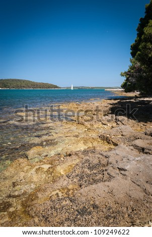 Rocky Croatian beach with  sailing boat in background- area of Pula, Adriatic sea.
