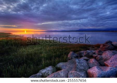Rocky grass along a river at sunset - stock photo
