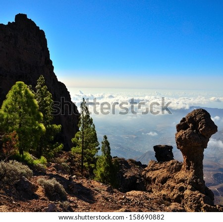 Rocky  landscape of Gran canaria with roques, cliffs and pine trees in foreground, and sea of clouds with intense blue sky in background, view from above, Canary islands - stock photo