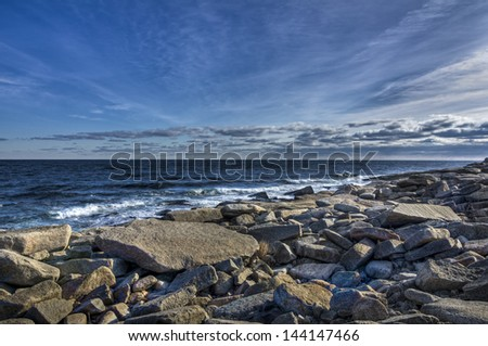 Rocky Massachusetts beach in winter with cold sky - stock photo