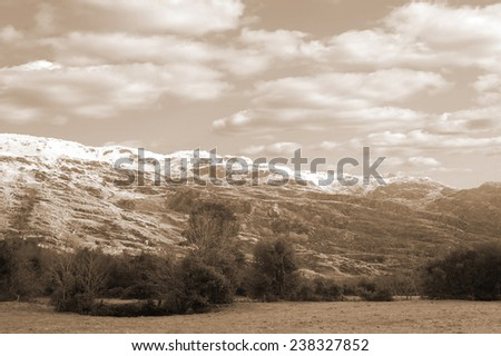 rocky mountain and fields countryside snow scene in irish speaking area of county Kerry Ireland with copy space - stock photo