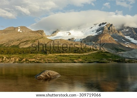Rocky mountains and lake with a reflection in Canada in the early evening light - stock photo