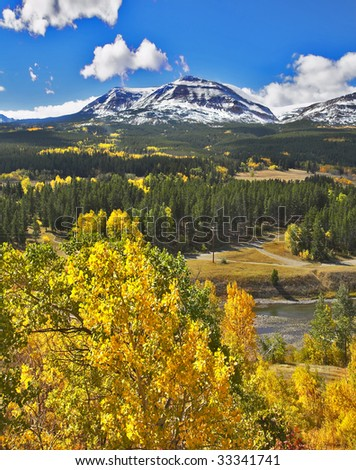 Rocky mountains, cold lake and charming green fur-trees - stock photo