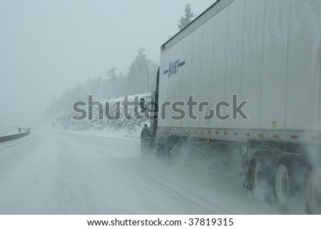 ROCKY MOUNTAINS, COLORADO - JANUARY 26 : Traffic speeds along icy and snowy roads on January 26, 2009 in Rocky Mountains, CO. - stock photo