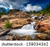Rocky Mountains national park, glacier waterfall in daylight with clouds. - stock photo