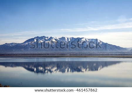 rocky mountains reflected into the great salt lake on antelope island