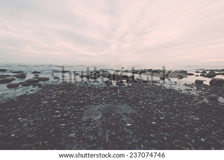 rocky sea beach with wide angle perspective over the sea clouds - retro, vintage style look - stock photo