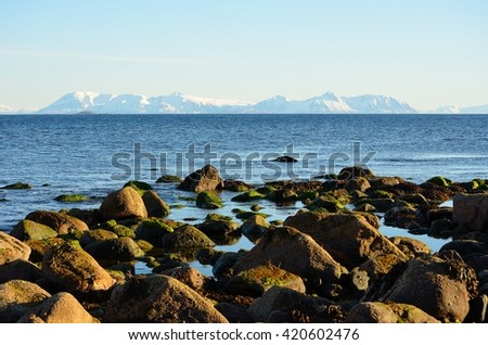 Rocky sea shore with snowy mountain range in the background on Grunnfarnes, Senja